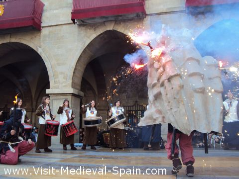 A traditional Catalonian Correfoc or running fire - A fibreglass dragon adorned with burning fireworks dances surrounded by drummers in Medieval costume .Manresa Medieval 2011, Catalonia Spain