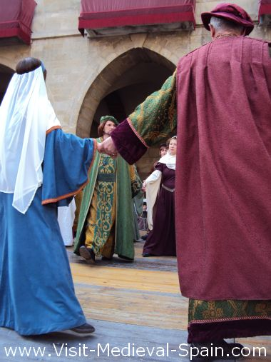 Dancers in traditional medieval costume perform a dance on stage in front of Manresa town hall