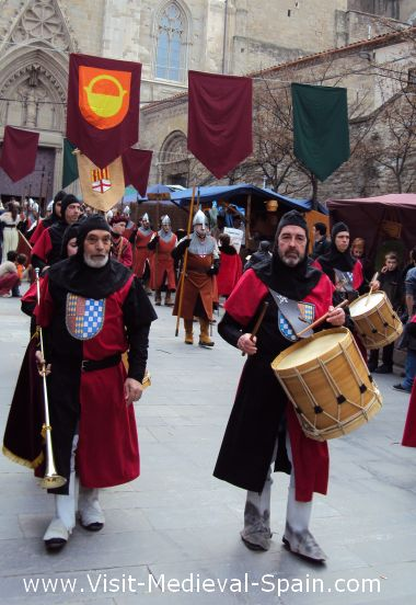 Medieval knights in armour, drummers and musicians on parade in front of the cathedral, Manresa Spain.