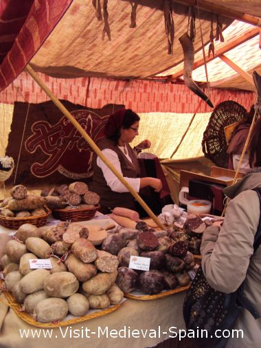 This photograph shows a stallholder in traditional medieval dress hard at work selling traditional food in her medieval market stall.Participants in the Fira de L'Aixada, Catalonia Spain